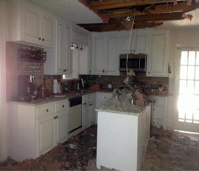 kitchen with fallen ceiling and light fixture after fire damage