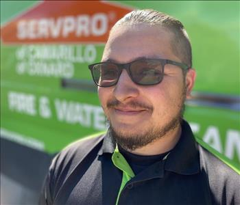 Portrait of Andres, male employee in front of green truck