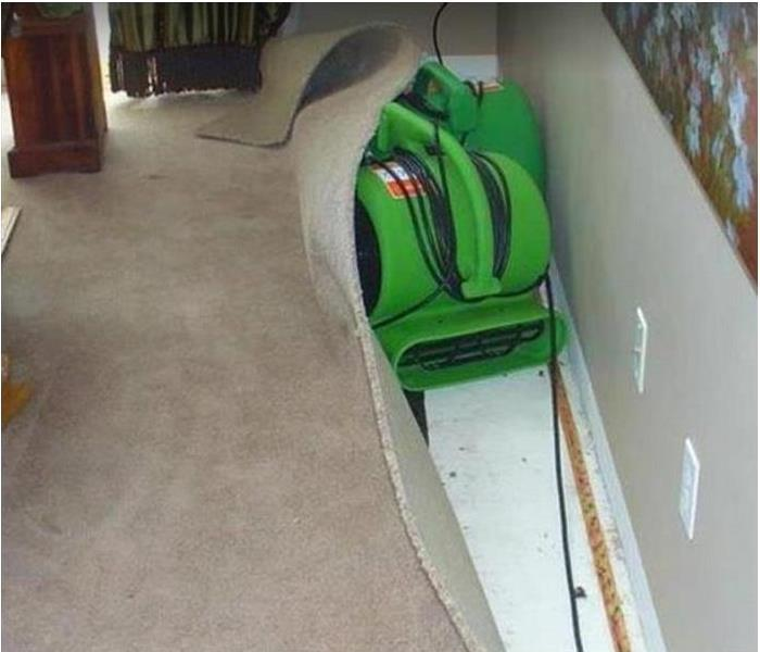 water damaged room. carpeting pulled back from wall as SERVPRO drying equipment dries floor and drywall