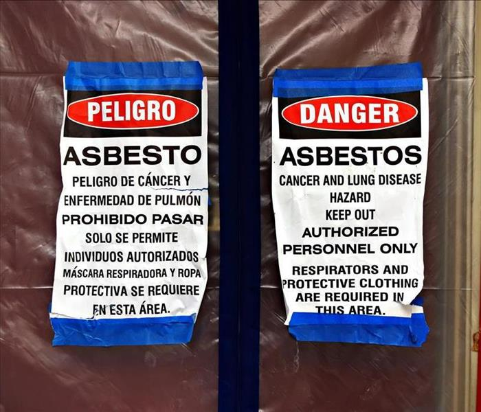 Sign in Spanish and English warning of asbestos danger on a window